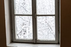 Window with winter landscape, tree branches covered with snow royalty free stock images