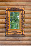 Window with wooden architraves in the wooden house Royalty Free Stock Photo