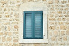 Window with wooden blinds. Window shut with wooden blinds of a coastal stone house Stock Photography
