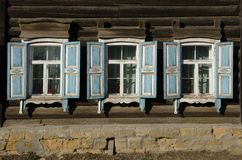 The window with the wooden carved architrave in the old wooden house in the old Russian town. royalty free stock image