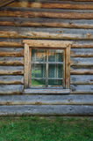 The window with the wooden carved architrave in the old wooden house in the old Russian town. royalty free stock photography