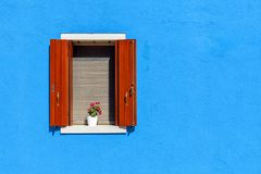 Window on blue wall in Burano, Italy. Royalty Free Stock Photo