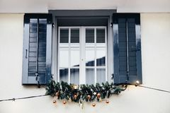 Window with wooden shutters festively decorated for Christmas holidays with lights and christmas tree twigs. stock image