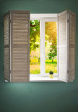 Window with wooden shutters. Window in turquoise wall with wooden shutters overlooking the garden Royalty Free Stock Images