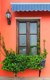 Window with wooden statue and ivy Stock Photo