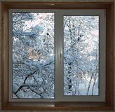 Window with a wooden window sill overlooking the snow-covered ga Stock Photography