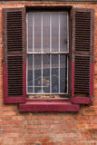 Window with Worn Out Wooden Shutters. Open window shutters on an old, crumbling building Royalty Free Stock Image