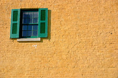 Window in yellow and green. Detail: shuttered window on painted brick wall Stock Photography