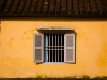 Window in Yellow Wall. Shuttered Window in Yellow Wall of Old Building in Hoi An, Vietnam Stock Photo