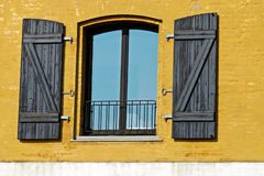 Window in a yellow wall Stock Photography