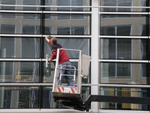 Windowclean. Window cleaner working on a glass facade in a gondola stock images