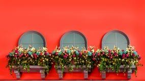 Windows和花在红色pannel阳台  免版税库存照片