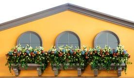 Windows和花在黄色阳台在顶面房子里 免版税图库摄影