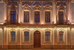 Windows, дверь и балконы на фасаде ночи жилого дома Стоковые Изображения RF