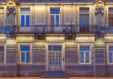 Windows, дверь и балкон на фасаде ночи жилого дома Стоковое Изображение