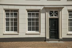 Windows и деревянная дверь серого элегантного фасада здания на солнечный день в Weesp Стоковое Фото