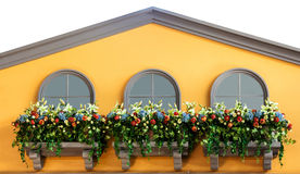 Windows и цветки на балконе желтого цвета в верхнем доме Стоковая Фотография RF