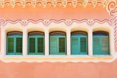 Windows на розовой стене дома Стоковые Изображения