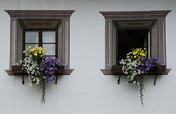 Windows. Flowers and old windows with painted frames in Austrian village Pettneu in Arlberg Stock Photography
