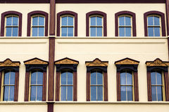 Windows adornado en el edificio amarillo del yeso Foto de archivo