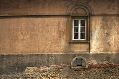 Windows with arch relief on forgotten decaying wall. Windows with arch relief on forgotten empty wall painted with many layers of fading warm tones royalty free stock photography