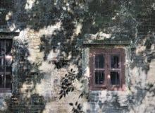 Windows auf gealterter Wand im Schatten Stockbild