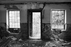 Windows avec des barres et une porte ouverte d'un bâtiment abandonné de la photo noire et blanche d'intérieur Image stock