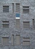 Windows avec des volets dans le modèle gris de mur de ville Images stock