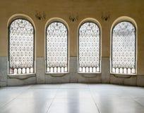 Windows avec du fer a décoré la grille, le mur jaune, et le plancher de marbre Image libre de droits