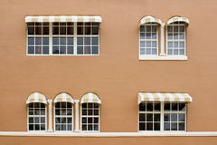 Windows with awnings on a brown wall. White windows with sun shades on a brown wall Stock Photo