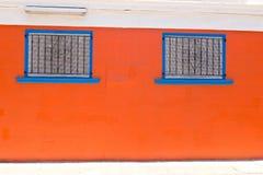 Windows azul contra la pared anaranjada Fotografía de archivo libre de regalías