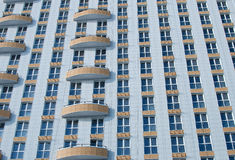 Windows and balconies of high-rise building. Close up of a white house with yellow balconies and blue windows Royalty Free Stock Photo