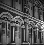 Windows and balconies in typical colonial architecture in Singapore China Town shot in black and white analogue film photography. At night royalty free stock photography