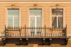 Windows and balcony on facade of apartment building. Two windows and door in a row and balcony on facade of urban apartment building front view, St. Petersburg Royalty Free Stock Image