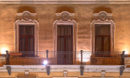 Windows and balcony on night facade of office building Stock Photo