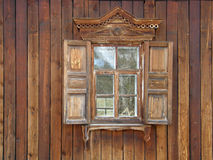The windows with beautiful architraves in old wooden house. Stock Photography
