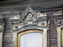 The windows with beautiful architraves in old wooden house. Ulan Royalty Free Stock Photo