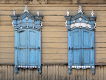 The windows with beautiful architraves in old wooden house. Ulan Stock Image