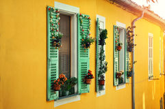 Windows with beautiful floral decoration on a yellow house.Traditional mediterranean look. Royalty Free Stock Photography