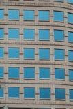 Windows bleu carré sur le bâtiment en pierre fleuri Images libres de droits