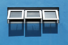 Windows and blue wall Royalty Free Stock Images
