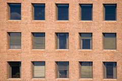 Windows in the brick wall. Section of exterior of a modern office building with repetitive pattern of windows Royalty Free Stock Photos