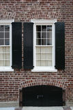 Windows, brick wall, black shutters Stock Photography