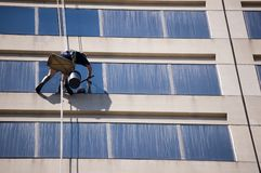 Windows cleaner. A windows cleaner are working on boson's chair on high-rise building stock photography