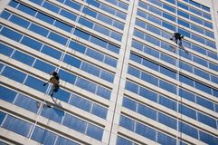 Windows cleaners. Two windows cleaners are working on boson's chair on high-rise building stock images