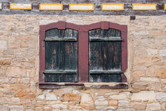 Windows with closed shutters in a sandstone wall Royalty Free Stock Images