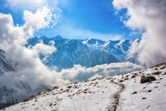 Windows of clouds in mountains. Beautiful misty rock landscape with snow and clouds. Great view of the foggy Ala-Archa National Park in Kyrgyzstan royalty free stock photo