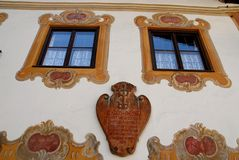 Windows with coat of arms and frescoes in Oberammergau in Germany. Photo made in Oberammergau in Bavaria (Germany). The picture shows one of the typical houses Royalty Free Stock Images