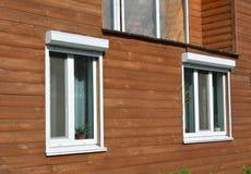 Windows com o obturador de rolamento no exterior de madeira da fachada da casa Fotos de Stock