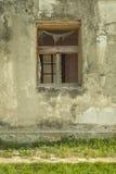 Windows com vidro quebrado na casa branca abandonada da vila Foto de Stock